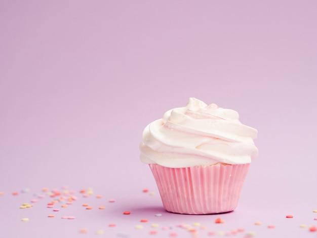 Muffin di compleanno semplice su sfondo rosa