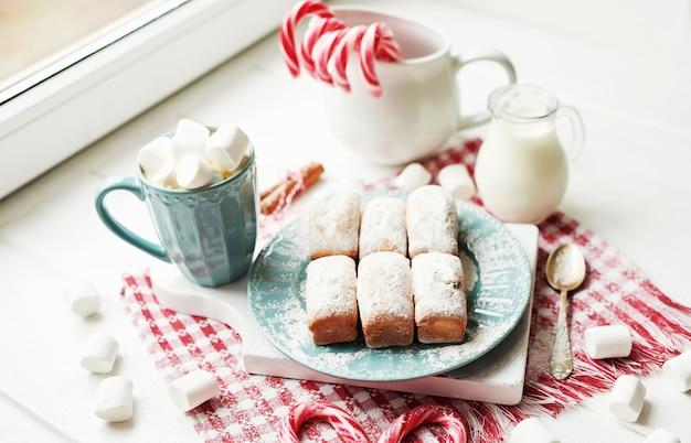 Muffin di natale, latte, cacao, caramelle gommosa e molle, caramelle lecca-lecca sul piatto vicino alla finestra