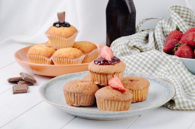 Muffin di vista laterale con fragole e muffin con cioccolato sui piatti con le fragole