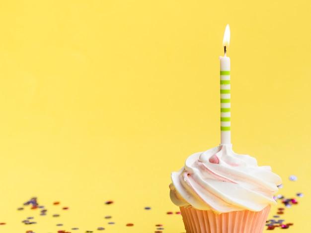 Muffin e candela semplici di compleanno del primo piano