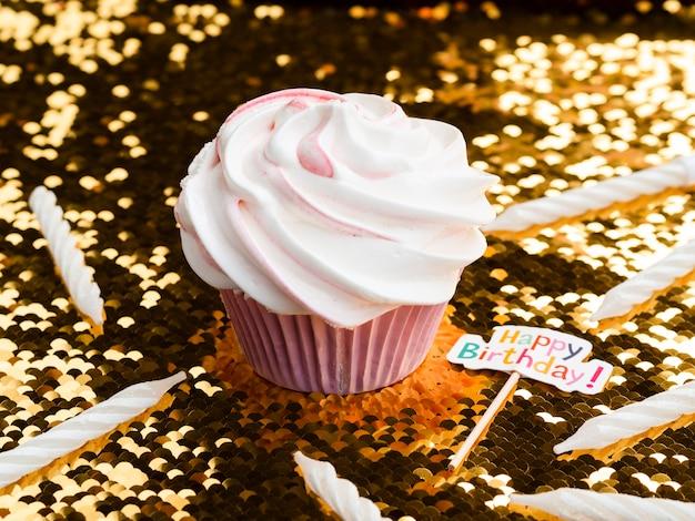 Muffin e candele deliziosi di compleanno del primo piano