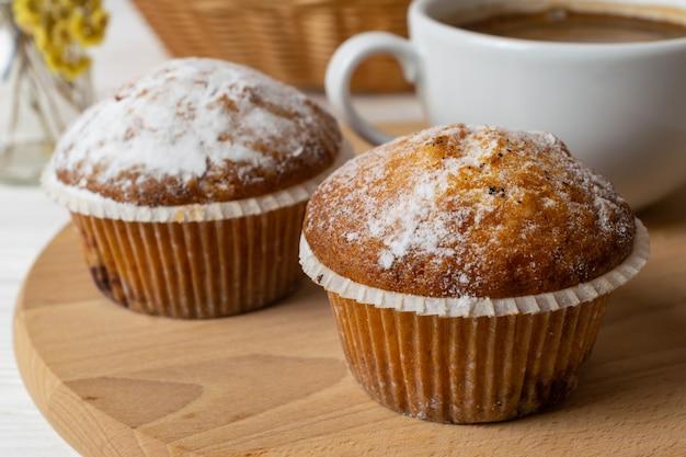 Muffin fatti in casa freschi con zucchero in polvere e una tazza di caffè