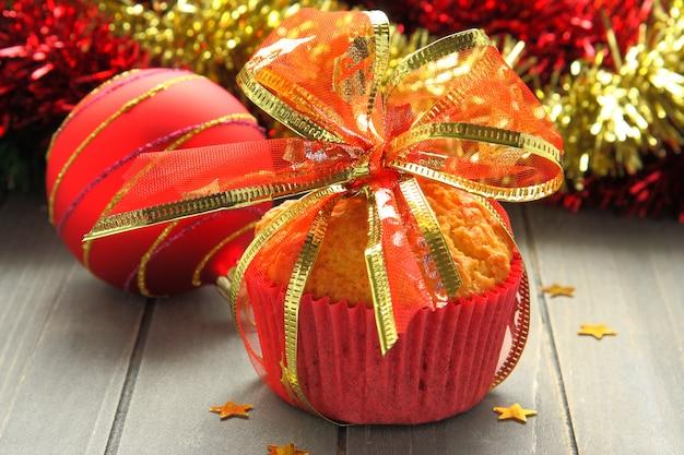 Muffin in tazze rosse con decorazioni natalizie