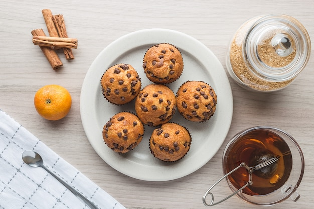 Muffin, tazza di tè, zucchero, mandarino e cannella