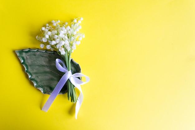Mughetti legati con nastro su giallo. copia . fiori di primavera