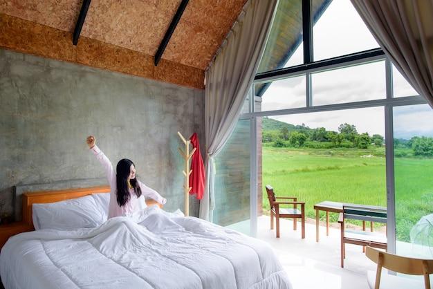 Mujer asiática acaba de despertar de la cama en una habitación con paisaje