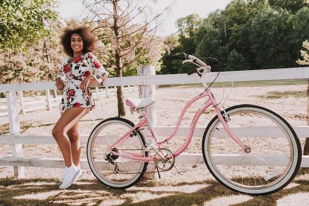 Mulatta girl si trova accanto alla pista da corsa con la bici