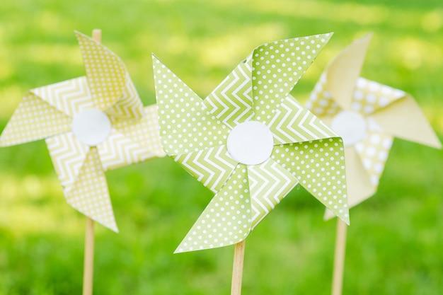 Mulini a vento di carta su uno sfondo di erba verde