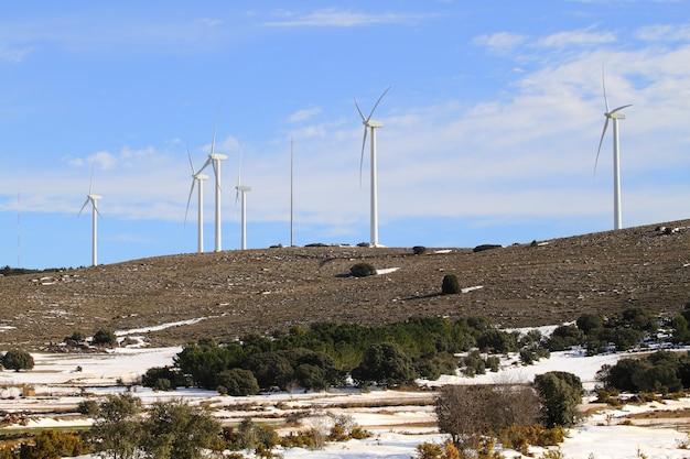 Mulini a vento elettrici aerogeneratore sulla montagna di neve