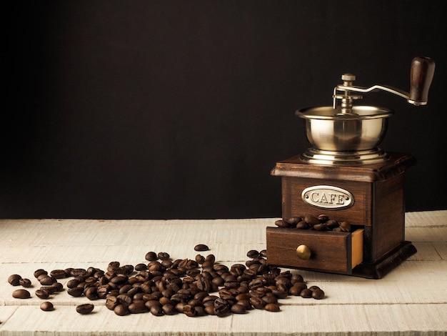 Mulino d'annata del macinacaffè del primo piano con i chicchi di caffè su un fondo di legno scuro e leggero.
