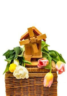 Mulino decorativo di legno con i tulipani su una priorità bassa bianca.