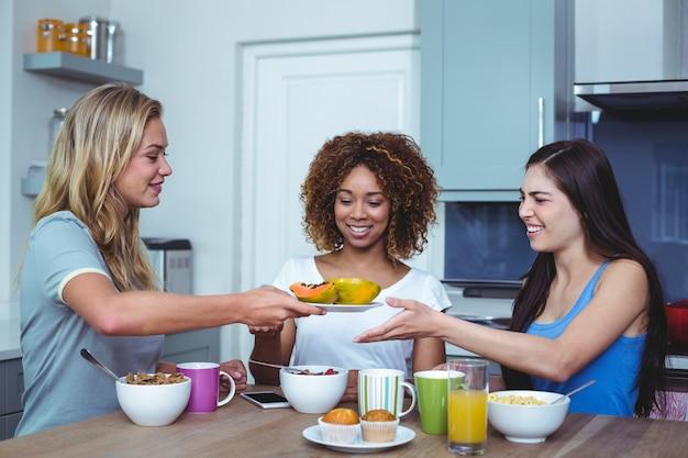Multi amici etnici che tengono piatto con papaia in casa