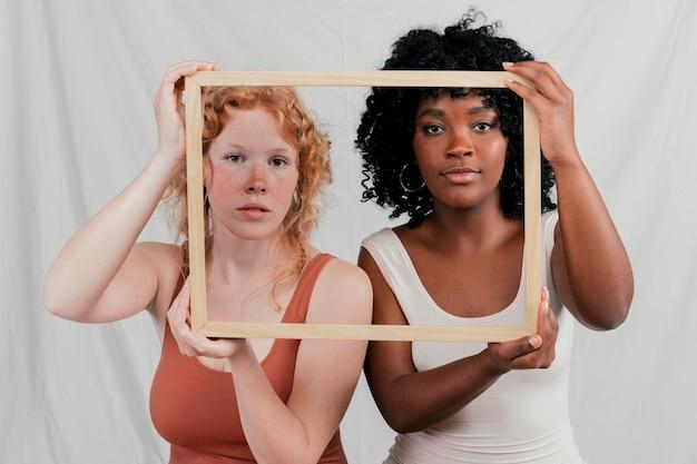 Multi amico femminile etnico che esamina macchina fotografica attraverso la struttura di legno contro il contesto grigio