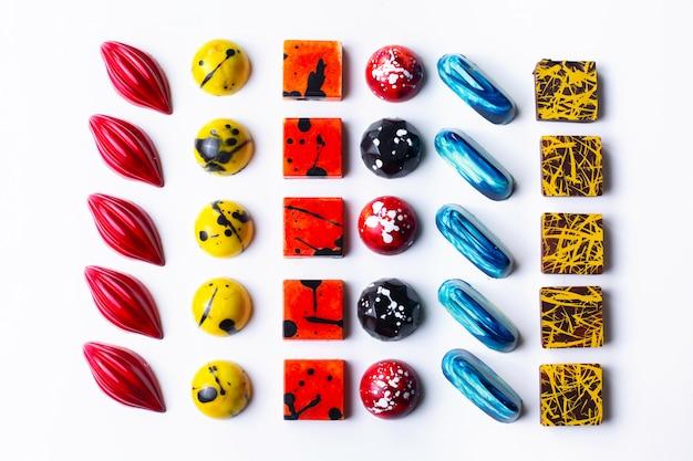Multi dolci colorati del cioccolato di vista superiore su bianco