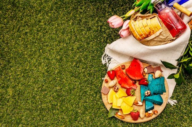 Multi formaggio e cestino colorati assortiti con pane e vino e succo di fragola su erba verde artificiale