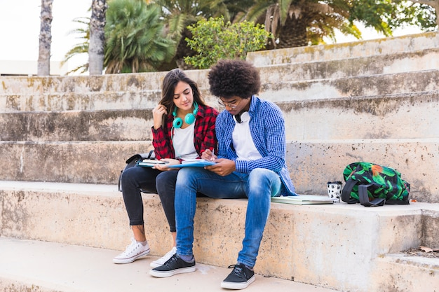Multi giovani coppie etniche che si siedono sulla scala che studia insieme nel parco