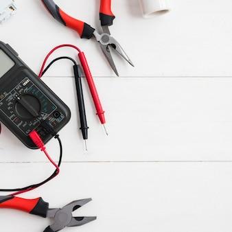 Multimetro digitale con tester e pinze sul tavolo di legno bianco