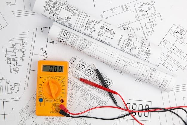 Multimetro digitale e disegni elettrotecnici cartacei
