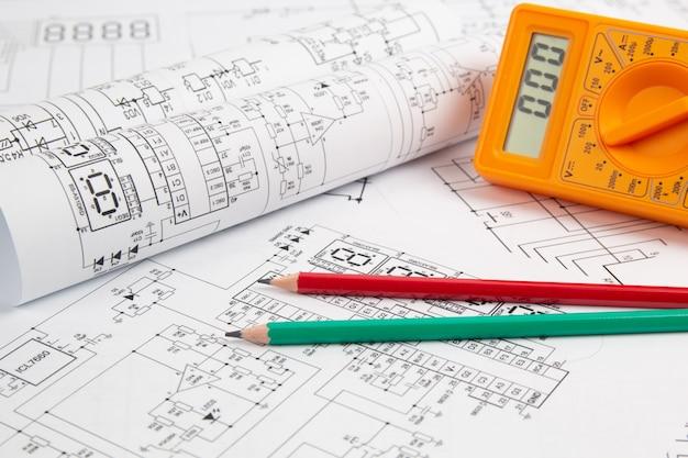 Multimetro digitale e matite su disegni di ingegneria elettrica di carta