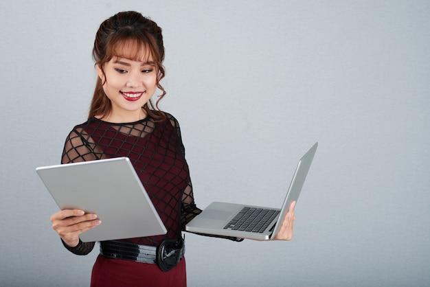 Multitasking della donna di affari di beauitiful sul pc del computer portatile e della compressa