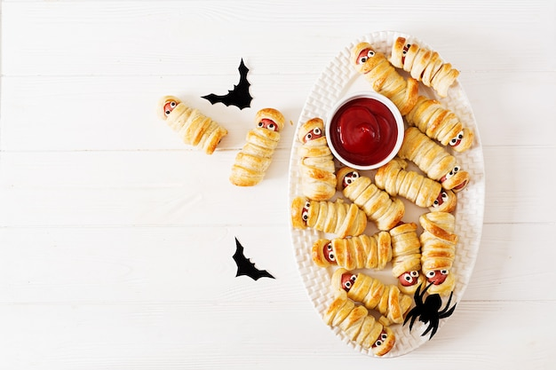 Mummie spaventose della salsiccia in pasta con gli occhi divertenti sulla tavola. decorazione divertente. cibo di halloween. vista dall'alto. disteso