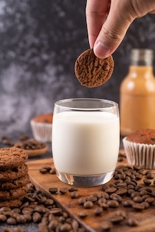 Munga in un bicchiere, completo di chicchi di caffè, cupcakes, banane e biscotti su un piatto di legno.