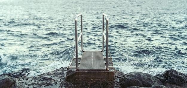 Muoversi verso l'oceano sulla spiaggia con le pietre.