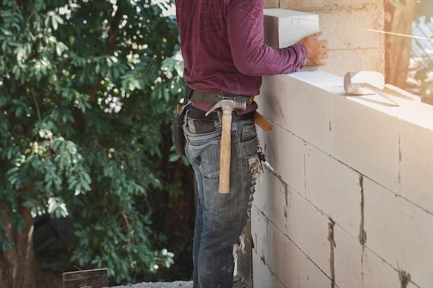 Muratore che installa i mattoni sul cantiere