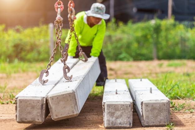Muratore che scarica il palo concreto dal camion