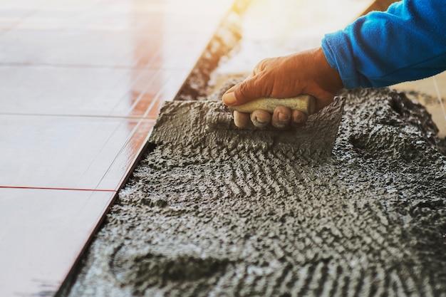 Muratore della mano del primo piano che pone mattonelle sul pavimento