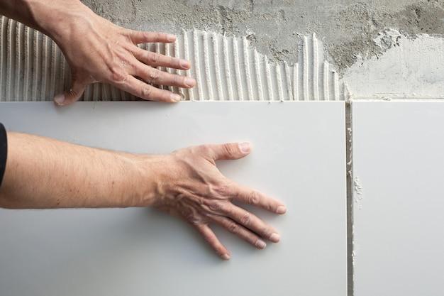 Muratore di costruzione uomo mani sul lavoro di piastrelle