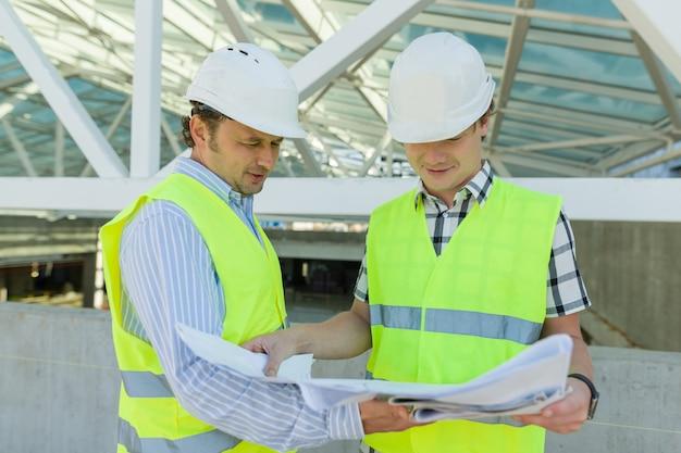 Muratore e ingegnere maschii al cantiere