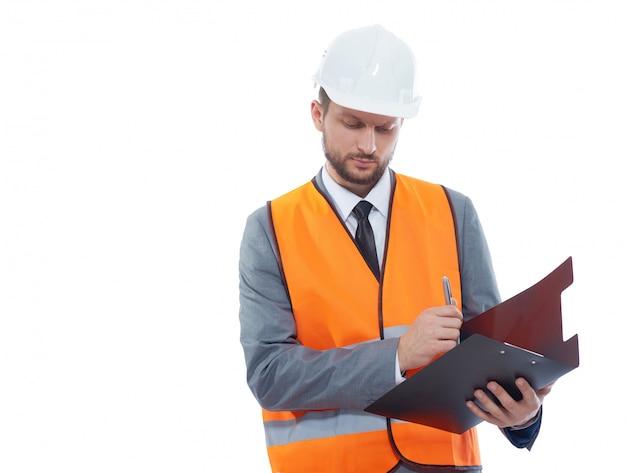 Muratore maschio che indossa giubbotto di sicurezza fluorescente e un elmetto protettivo che fa le note sui suoi appunti isolati sul bianco