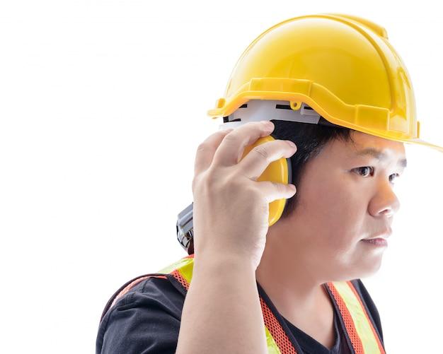 Muratore maschio con le attrezzature di sicurezza ed il primo piano standard della costruzione alle cuffie isolate