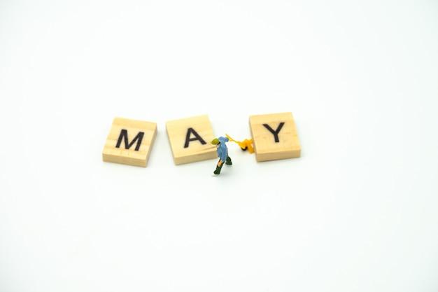 Muratore miniatura della gente che sta con il mese di legno di parola.