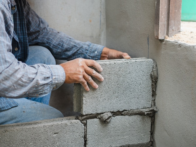 Muratore professionista che pone i mattoni con cemento.