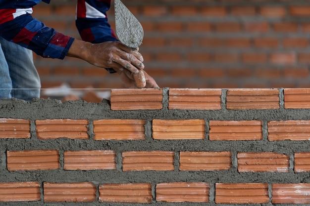 Muratore professionista della mano del primo piano che pone i mattoni nel nuovo sito industriale