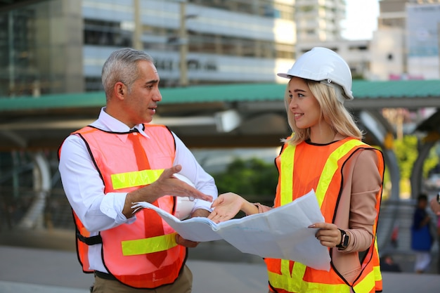 Muratori che esaminano i modelli sul cantiere