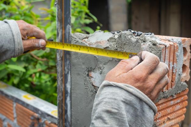 Muratura. muratore che costruisce un muro di mattoni.