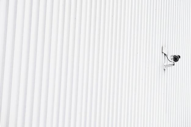 Muro a strisce della costruzione con una videocamera di sicurezza
