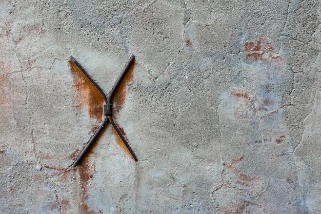 Muro di cemento con crepe e staffe metalliche a forma di croce.