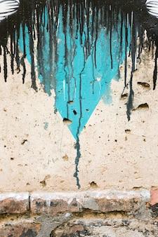 Muro di cemento con gocce di vernice e mattoni