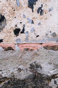 Muro di cemento con mattoni e macchie di sporco
