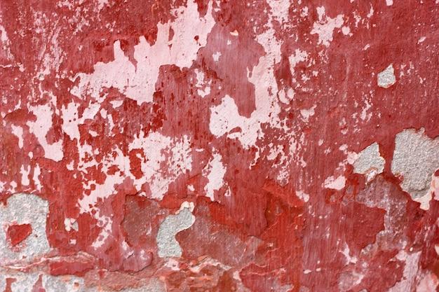 Muro di cemento con vernice rossa, sfondo ruvido. fondo concreto astratto con la vecchia pittura rossa della sbucciatura.