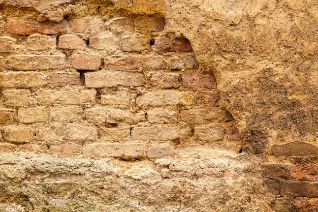 Muro di cemento invecchiato con mattoni