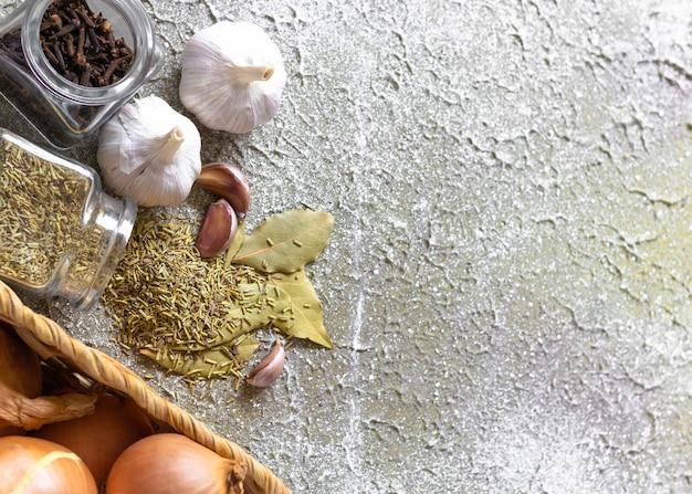 Muro di ingredienti piccanti. cipolla, aglio, rosmarino e chiodi di garofano sul muro di cemento grigio. design piatto con spazio di copia