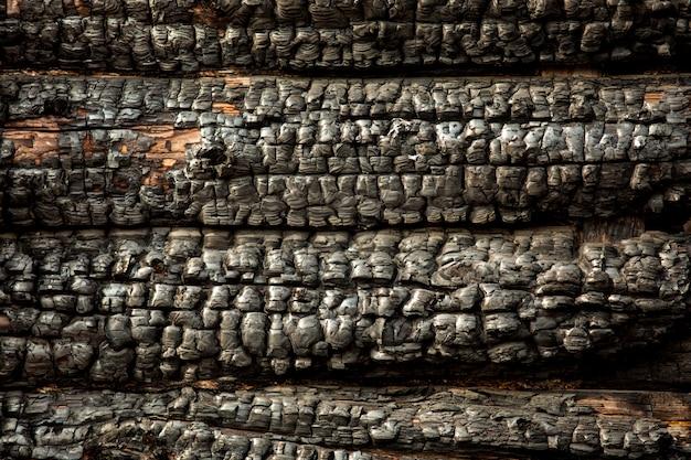 Muro di legno carbonizzato carbonizzato nero. consistenza ruvida. conseguenze dopo l'incendio. frammento della casa bruciata