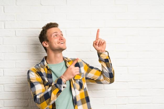 Muro di mattoni bianco dell'uomo bello biondo che indica con il dito indice una grande idea