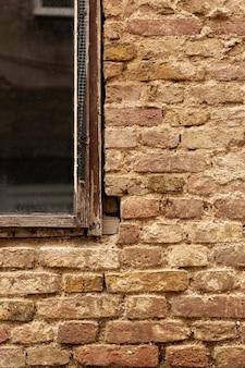 Muro di mattoni con finestra invecchiata