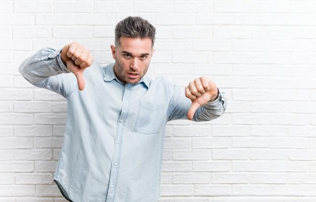 Muro di mattoni contro il giovane uomo bello che mostra pollice verso il basso e che esprime antipatia.